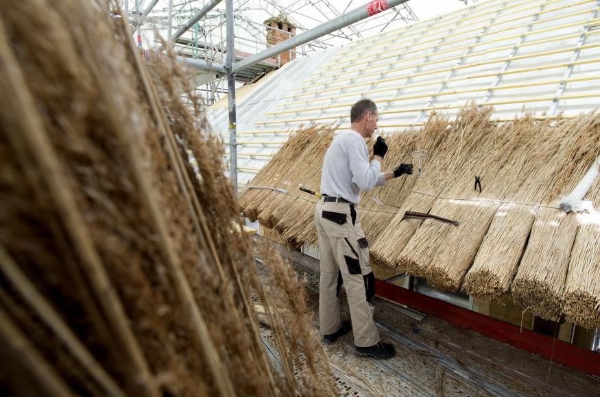 Sur les autres bâtiments et la galerie la couverture en chaume est rétablie de nouveaux faitages en argile avec des plantations traditionnelles sont